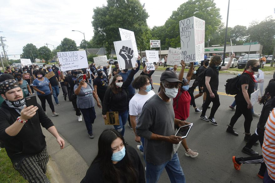 Protesters march down Beattie Ford Road near Charlotte-Mecklenburg Police Department-Metro Division station during a rally over the death of George Floyd in Minneapolis on Friday, May 29, 2020, in Charlotte, N.C.  (David T. Foster III/The Charlotte Observer via AP)