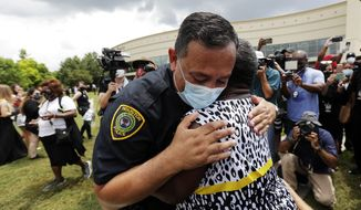 Houston Police Chief Art Acevedo and Charlene Davis embrace after Davis prayed for him as she stood in line at a public visitation for George Floyd at The Fountain of Praise church in Houston, Monday, June 8, 2020, in Houston.(AP Photo/Eric Gay)