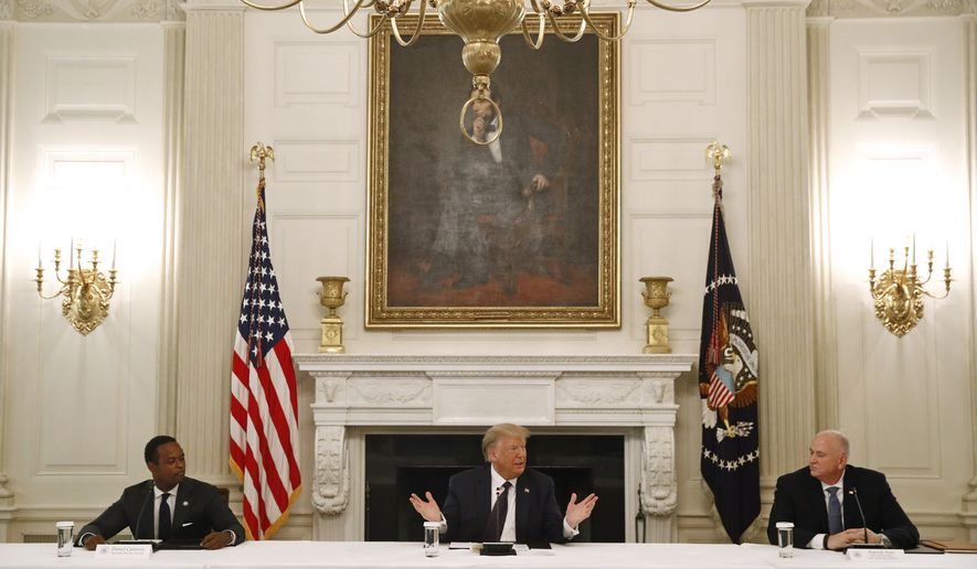 President Donald Trump speaks during a roundtable discussion with law enforcement officials, Monday, June 8, 2020, at the White House in Washington. Seated with Trump are Kentucky Attorney General Daniel Cameron, left, and Pat Yoes, National President of the Fraternal Order of Police. (AP Photo/Patrick Semansky)