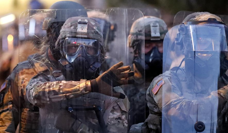Georgia National Guard troops prepare to enforce a 9:00 pm curfew as demonstrators chant, Tuesday, June 2, 2020, in Atlanta. Protests continued following the death of George Floyd, who died after being restrained by Minneapolis police officers on May 25. (AP Photo/John Bazemore)