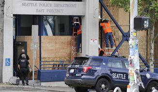 Workers put up plywood over the windows of a Seattle police precinct Monday, June 8, 2020, in Seattle, where protests continued the night before over the death of George Floyd, a black man who was in police custody in Minneapolis. Just days after Seattle's mayor and police chief promised a month-long moratorium on using a type of tear gas to disperse protesters, the department used it again. (AP Photo/Elaine Thompson)