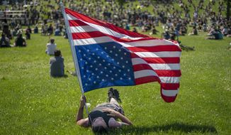 "Rory Wakemup holds an upside-down United States flag at ""The Path Forward"" meeting, a meeting between city council and community members, at Powderhorn Park, Sunday, June 7, 2020, in Minneapolis. The focus of the meeting was to defund the Minneapolis Police Department. ( Jerry Holt/Star Tribune via AP)"