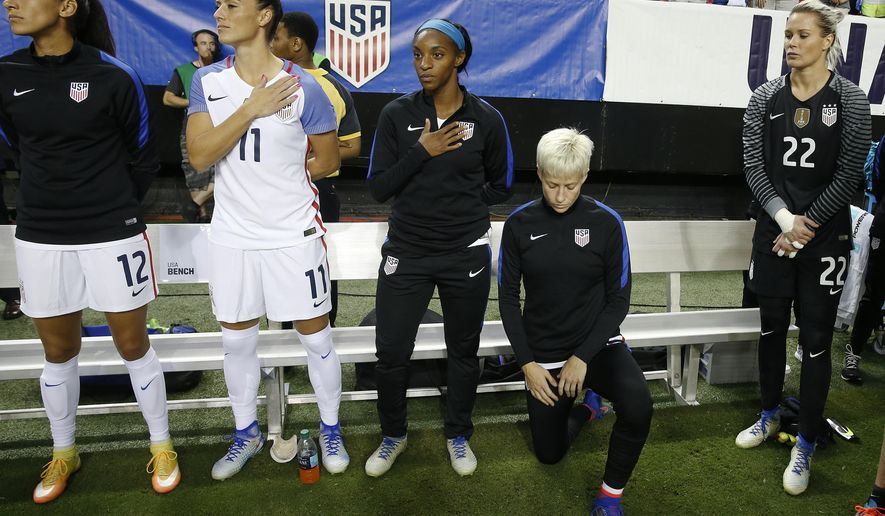 In this Sept. 18, 2016, file photo, United States' Megan Rapinoe, right, kneels next to teammates Christen Press (12), Ali Krieger (11), Crystal Dunn (16) and Ashlyn Harris (22) as the national anthem is played before the team's exhibition soccer match against the Netherlands in Atlanta. The U.S. women's national team wants the U.S. Soccer Federation to repeal the anthem policy it instituted after Rapinoe started kneeling during the national anthem. The U.S. women's team also wants the federation to state publicly that the policy was wrong and issue an apology to the team's black players and supporters. (AP Photo/John Bazemore, File)  **FiLE**