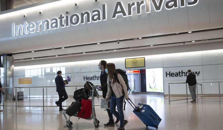 Passengers wearing face masks arrive on the first day of new rules that people arriving in Britain from overseas will have to quarantine themselves for 14 days to help stop the spread of coronavirus, at Heathrow Airport in London, Monday, June 8, 2020. The British government has said that anyone caught not complying with the quarantine will face a fine. (AP Photo/Matt Dunham)