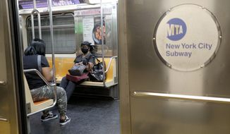 Commuters ride uncrowded subways in New York, Monday, June 8, 2020. After three months of a coronavirus crisis followed by protests and unrest, New York City is trying to turn a page when a limited range of industries reopen Monday. (AP Photo/Seth Wenig)