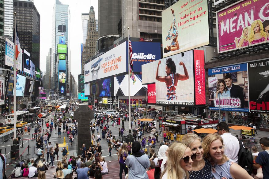 In this June 20, 2019, file photo, tourists visit Times Square in New York. After three months of a coronavirus crisis followed by protests and unrest, New York City is trying to turn a page when a limited range of industries reopen Monday, June 8, 2020. (AP Photo/Mark Lennihan, File)