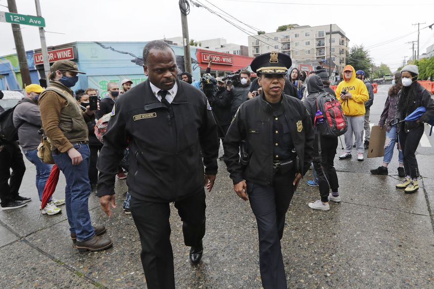 Seattle Police Chief Carmen Best, right, and Seattle Fire Chief Harold Scoggins head out after Best spoke with demonstrators near a closed Seattle police precinct Tuesday, June 9, 2020, in Seattle, following protests over the death of George Floyd, a black man who was in police custody in Minneapolis. (AP Photo/Elaine Thompson)