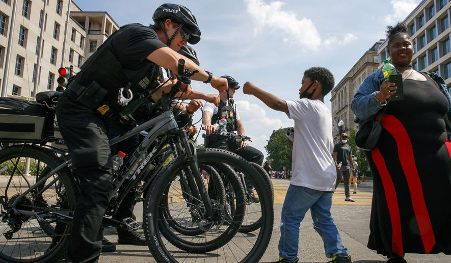 Josiah Brown, 6, of Washington, fist bumps a member of the U.S. Secret Service police after and his mother, Alexis Brown, right, prayed over the officers while visiting the site of protests, Tuesday, June 9, 2020, near the White House in Washington. The protests began over the death of George Floyd, a black man who was in police custody in Minneapolis. Floyd died after being restrained by Minneapolis police officers. (AP Photo/Jacquelyn Martin)