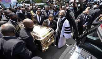 The funeral home team pushes the casket of George Floyd into the hearse as the Rev. Al Sharpton, right, looks on after the funeral service for George Floyd at The Fountain of Praise church Tuesday, June 9, 2020, in Houston. (AP Photo/David J. Phillip, Pool)