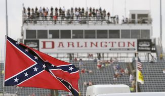 FILE - In this Sept. 5, 2015, file photo, a Confederate flag flies in the infield before a NASCAR Xfinity auto race at Darlington Raceway in Darlington, S.C. Bubba Wallace, the only African-American driver in the top tier of NASCAR, calls for a ban on the Confederate flag in the sport that is deeply rooted in the South. (AP Photo/Terry Renna, File)