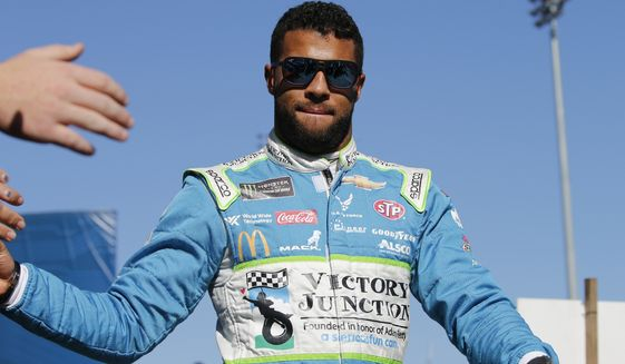 In this Oct. 27, 2019, photo, Bubba Wallace greets fans during a NASCAR Cup Series race at Martinsville Speedway in Martinsville, Va. (AP Photo/Steve Helber) **FILE**