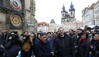 FILE - In this file photo taken Monday, Jan. 13, 2020, mayor of Prague Zdenek Hrib, left, and Taipei city mayor Ko Wen-je shake hands before signing a partnership agreement between the two cities at the Old Town Square in Prague, Czech Republic. Speaker of the upper house of the Czech Parliament Milos Vystrcil announced on Tuesday June 9, 2020, that he will visit Taiwan despite threats from China. Vystrcil said he would be accompanied by a business delegation on his visit that is preliminary scheduled to open on August 30. (AP Photo/Petr David Josek, File)