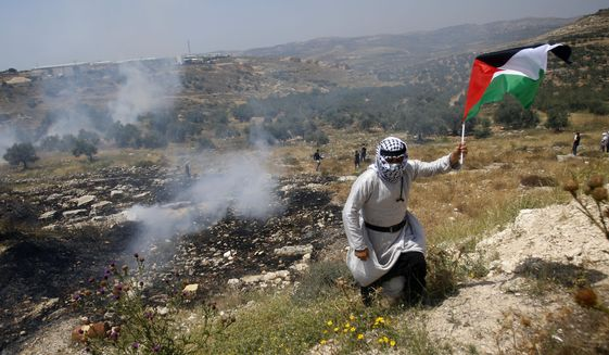 Palestinians run away from tear gas fired by Israeli soldiers during a protest against Israel's plan to annex parts of the West Bank and Trump's mideast initiative ,in the West Bank village of Qusin near Nablus Friday, Jun. 5, 2020.(AP Photo/Majdi Mohammed)