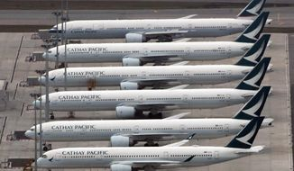 FILE - In this March 6, 2020, file photo, Cathay Pacific Airways aircraft line up on the tarmac at the Hong Kong International Airport. Financially battered Hong Kong airline Cathay Pacific Airways says it is proposing the government help fund a $5 billion recapitalization plan to help it recover from the coronavirus pandemic. (AP Photo/Kin Cheung)