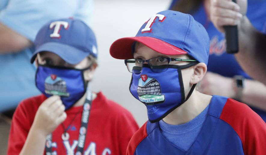 FILE - In this June 1, 2020, file photo, Gavin Bollmer, left, and his buddy, Austin LaFountain, wear Globe Life Field masks as they tour the home of the Texas Rangers baseball team in Arlington, Texas. Many organizations are trying to bridge the budget gap from the coronovirus through enhanced sponsorship sales, such as temporary billboards that could be stretched over unsold sections of seats. Teams and leagues are selling branded face masks and other personal protective equipment. Almost all of them are trying to engage fans in new and creative ways. It won't come close to making up the budget shortfall, but the hope is to survive long enough for sports to return to normal. (AP Photo/LM Otero, File)