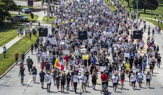 Marchers walk along a street during a rally to remember James Scurlock on Sunday, June 7, 2020, in Omaha, Neb. Scurlock was fatally shot by a white bar owner during an Omaha protest over George Floyd's death. (Chris Machian/Omaha World-Herald via AP)