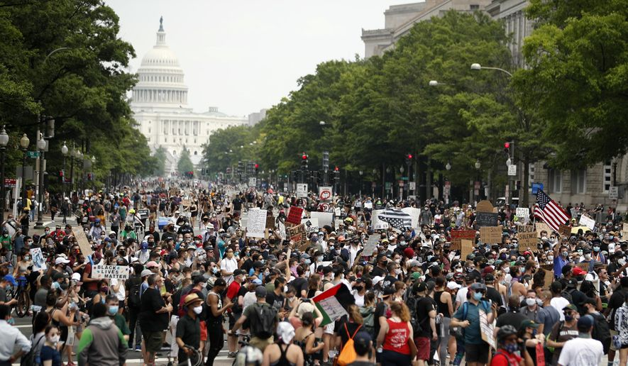 In this June 6, 2020, file photo, demonstrators walk on Pennsylvania Avenue as they protest over the death of George Floyd, a black man who died after being restrained by Minneapolis police officers. A democratic government that is amenable to the changes may enact legislation, or a change of leadership can be forced at the ballot box. (AP Photo/Andrew Harnik, File)