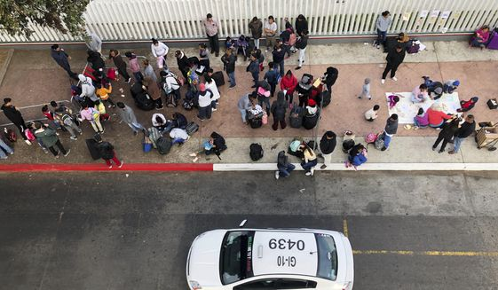 In this Nov. 10, 2019, file photo, migrants gather at the U.S.-Mexico border in Tijuana, Mexico, to hear names called from a waiting list to claim asylum in the U.S. (AP Photo/Elliot Spagat, File)