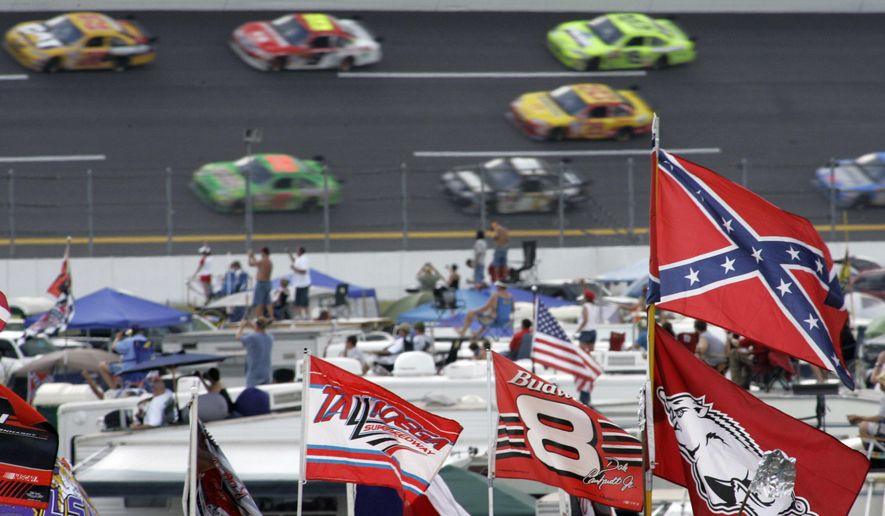 FILE - In this Oct. 7, 2007, file photo, a Confederate flag flies in the infield as cars come out of Turn 1 during a NASCAR auto race at Talladega Superspeedway in Talladega, Ala. NASCAR banned the Confederate flag from its races and venues Wednesday, June 10, 2020, formally severing itself from what for many is a symbol of slavery and racism.  (AP Photo/Rob Carr, File) **FILE**