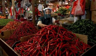 FILE - In this  June 2, 2020, file photo, a chili pepper vendor wears a face mask and shield as a precaution against the new coronavirus at a traditional market in Jakarta, Indonesia. As Indonesia's overall virus caseload continues to rise, Jakarta's governor has moved to restore normalcy by lifting some restrictions, saying that the spread of the virus in the city of 11 million has slowed down after peaking in mid-April. This has raised concerns among some, with experts warning that reopening too soon can cause Jakarta to be hit with a second wave of the virus. (AP Photo/Tatan Syuflana, File)