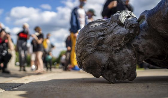 People stand around the fallen Christopher Columbus statue at the Minnesota state Capitol in St. Paul, Minn., Wednesday, June 10, 2020. (Evan Frost/Minnesota Public Radio via AP)