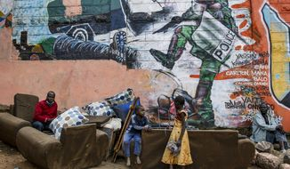 FILE - In this June 9, 2020, file photo, Kenyan children and men are photographed in the Kibera slum in Nairobi, Kenya, in front of a new mural showing an incident in 2016 when a Kenyan riot policeman repeatedly kicked a protester. The killing of George Floyd in the United States has raised awareness over police violence in South Africa and Kenya. (AP Photo/Brian Inganga, File)