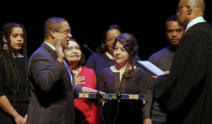 In this Monday, Jan. 7, 2019, file photo, former U.S. Rep. Keith Ellison, second from left, surrounded by family members, places his hand on the Koran as U.S. District Judge Michael Davis administers the oath of office for the new Minnesota attorney general during ceremonies in St. Paul, Minn. Taking over as lead prosecutor in George Floyd's death is giving Ellison a national platform to talk about race in America. (AP Photo/Jim Mone, File)