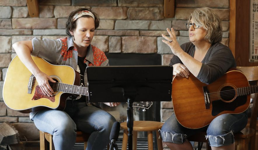 In this May 22, 2020, photo, nurse Megan Palmer, left, and care partner Anna Henderson, who both work at Vanderbilt University Medical Center, appear during a songwriting session at Henderson's home in Ashland City, Tenn. During the COVID-19 pandemic, their role as caregivers has become even more important as hospital visits from family and friends were limited or prohibited to prevent the spread of the virus. Music and songwriting has helped them express the complexity of emotions that comes with caregiving, especially in the time of a pandemic. (AP Photo/Mark Humphrey)