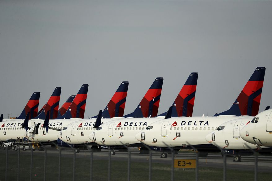 FILE - In this April 1, 2020 file photo, several dozen mothballed Delta Air Lines jets are parked at Kansas City International Airport in Kansas City, Mo. The skies are clearing up a bit for airlines as states ease lockdown measures and travelers slowly return to airport check-in lines. More airlines are restoring flights to their schedules and investors have taken note, driving up shares for the major airlines after a staggering decline.  (AP Photo/Charlie Riedel, File)