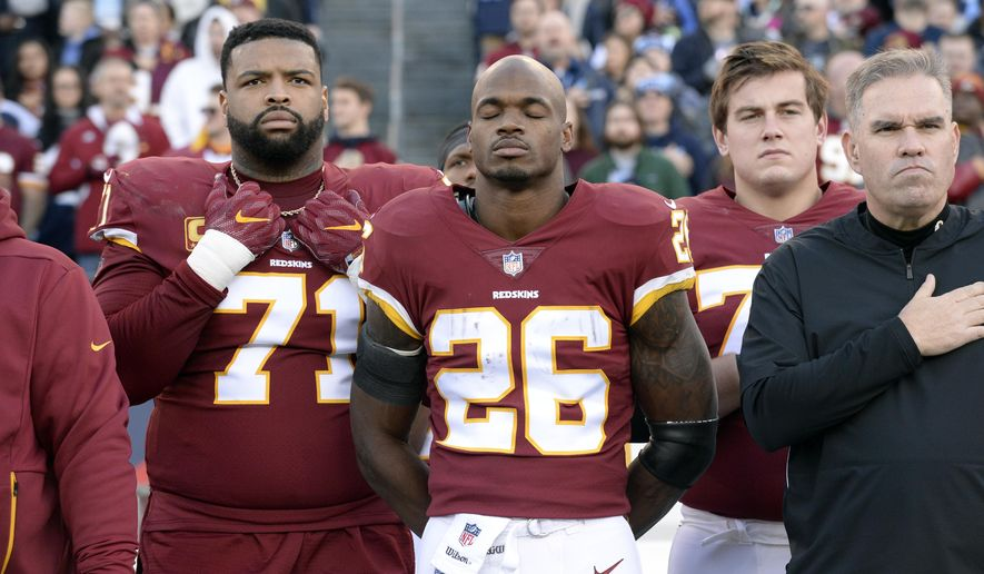In this Dec. 22, 2018, file photo, Washington Redskins running back Adrian Peterson (26) stands for the national anthem before an NFL football game against the Tennessee Titans in Nashville, Tenn. NFL players who want to kneel during the national anthem to protest police brutality and racism have far more support than Colin Kaepernick did  four years ago.  (AP Photo/Mark Zaleski, File) ** FILE **