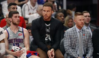 FILE - In this Jan. 27, 2020, file photo, Detroit Pistons forward Blake Griffin sits with guard Sviatoslav Mykhailiuk (19) and assistant coach Sean Sweeney during the first half of an NBA basketball game against the Cleveland Cavaliers in Detroit. With Andre Drummond traded and Blake Griffin's health again in question, the Detroit Pistons face an uncertain future. (AP Photo/Carlos Osorio, File)