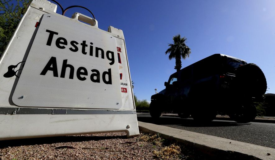 In this May 23, 2020, file photo, a vehicle arrives at COVID-19 testing site at Steele Indian School Park, in Phoenix. Coronavirus cases are rising in nearly half the U.S. states, as states are rolling back lockdowns. (AP Photo/Matt York, File)