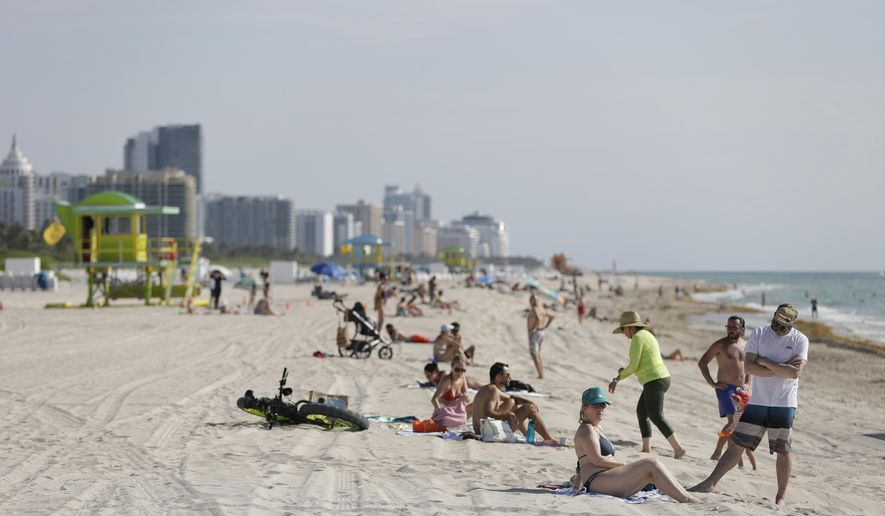 Beach goers enjoy a day on the sand and in the water, Wednesday, June 10, 2020, on Miami Beach, Florida's famed South Beach. (AP Photo/Wilfredo Lee)