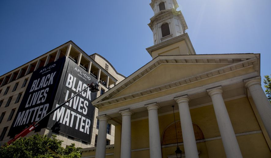 St. John's Episcopal Church is visible as a large banner that reads Black Lives Matter is hung from the AFL-CIO building on part of 16th Street renamed Black Lives Matter Plaza, a site of protests, Friday, June 12, 2020, near the White House in Washington. The protests began over the death of George Floyd, a black man who was in police custody in Minneapolis. Floyd died after being restrained by Minneapolis police officers. (AP Photo/Andrew Harnik)