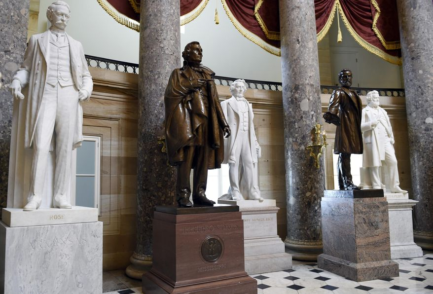 In this June 24, 2015, file photo, a statue of Jefferson Davis, second from left, president of the Confederate States from 1861 to 1865, is on display in Statuary Hall on Capitol Hill in Washington. House Speaker Nancy Pelosi is demanding that statues of Confederate figures such as Jefferson Davis be removed from the U.S. Capitol. (AP Photo/Susan Walsh, File)