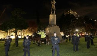 Police guard a statue of British explorer James Cook as protesters gather in Sydney, Friday, June 12, 2020, to support U.S. protests over the death of George Floyd. Hundreds of police disrupted plans for a Black Lives Matter rally but protest organizers have vowed that other rallies will continue around Australia over the weekend despite warnings of the pandemic risk. (AP Photo/Rick Rycroft)