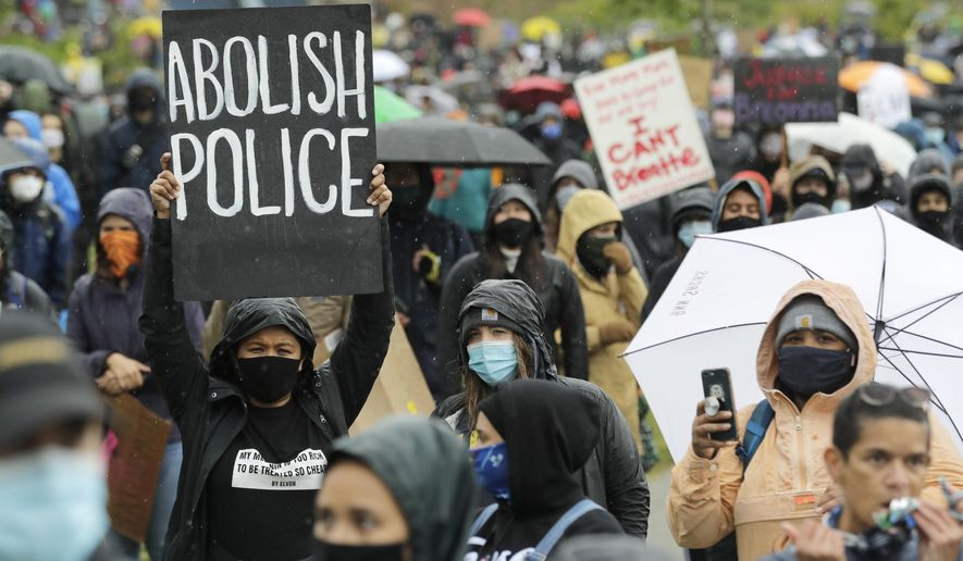 """A protester holds a sign that reads """"Abolish Police"""" during a """"Silent March"""" against racial inequality and police brutality that was organized by Black Lives Matter Seattle-King County, Friday, June 12, 2020, in Seattle. (AP Photo/Ted S. Warren) ** FILE **"""