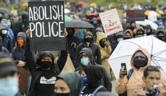 "A protester holds a sign that reads ""Abolish Police"" during a ""Silent March"" against racial inequality and police brutality that was organized by Black Lives Matter Seattle-King County, Friday, June 12, 2020, in Seattle. (AP Photo/Ted S. Warren) ** FILE **"