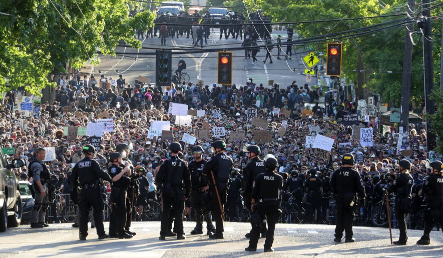 A sea of peaceful protesters are kept back from the Seattle Police Department's East Precinct on Capitol Hill, by a two-block buffer of officers and gates, seen in the foreground in Seattle, as demonstrations continue, sparked by the death of George Floyd in Minneapolis. (Ken Lambert/The Seattle Times via AP,File)