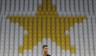 Juventus' Cristiano Ronaldo stands in front of the empty stands during an Italian Cup second leg soccer match between Juventus and AC Milan at the Allianz stadium, in Turin, Italy, Friday, June 12, 2020. The match was being played without spectators because of the coronavirus lockdown. (AP Photo/Luca Bruno)