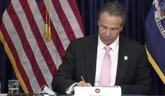 In this photo made from video provided by the office of New York Governor Andrew M. Cuomo, Gov. Cuomo, signs into law, Friday, June 12, 2020, in New York, a sweeping package of police accountability measures that received new backing following protests of George Floyd's killing. The laws signed by Cuomo, a Democrat, will ban police chokeholds, make it easier to sue people who call police on others without good reason, and set up a special prosecutor's office to investigate the deaths of people during and following encounters with police officers. (Office of New York Governor Andrew M. Cuomo via AP)