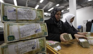 In this Jan. 13, 2010, file photo, Syrian employees stack packets of Syrian currency in the Central Syrian Bank in, Damascus, Syria. (AP Photo/Hussein Malla, File)