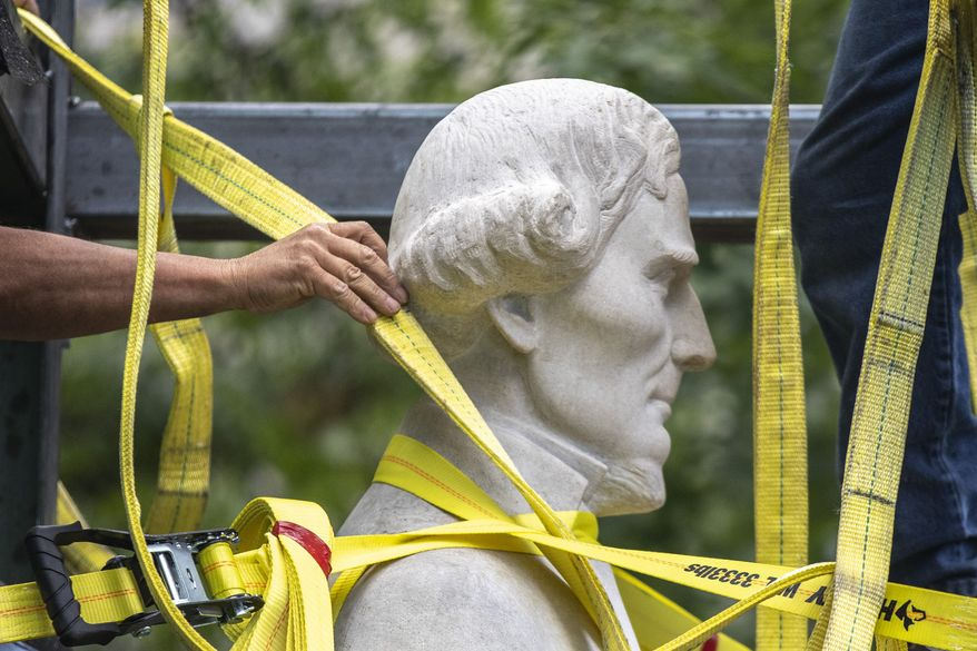 Workers secure a statue of Jefferson Davis to a trailer after removing it from the the Kentucky state Capitol in Frankfort, Ky., on Saturday, June 13, 2020. (Ryan C. Hermens/Lexington Herald-Leader via AP)