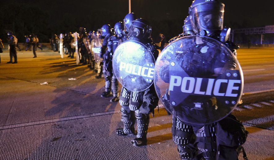After demonstrators got onto I75 and shut down the interstate, police line up in riot gear in Atlanta, Saturday, June 13, 2020. Demonstrators were protesting the death of Rayshard Brooks, a black man who was shot and killed by Atlanta police Friday evening following a struggle in a Wendy's drive-thru line. (Ben Gray/Atlanta Journal-Constitution via AP)