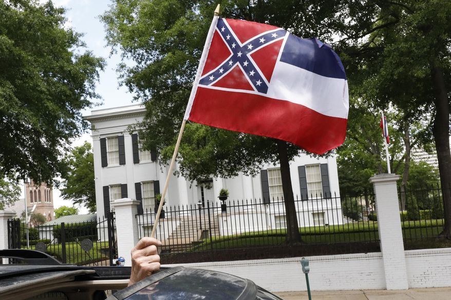 """In this April 25, 2020, file photograph, a small Mississippi state flag is held by a participant during a drive-by """"re-open Mississippi"""" protest past the Governor's Mansion, in the background, in Jackson, Miss. This current flag has in the canton portion of the banner the design of the Civil War-era Confederate battle flag, that has been the center of a long-simmering debate about its removal or replacement. (AP Photo/Rogelio V. Solis)"""