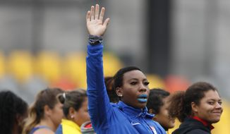 """FILE - In this Aug. 10, 2019, file photo, Gwendolyn """"Gwen"""" Berry of the United States waves as she is introduced at the start of the women's hammer throw final, during athletics competition at the Pan American Games in Lima, Peru. Berry won the gold medal. The U.S. Olympic and Paralympic Committee is signaling willingness to challenge longstanding IOC rules restricting protests at the Olympics, while also facing backlash from some of its own athletes for moves viewed by some as not being driven by sufficient athlete input. (AP Photo/Rebecca Blackwell, File)"""