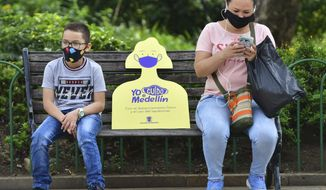 In this June 8, 2020 photo, a sign reminding citizens to maintain a safe social distance sits on a park bench between a woman and child, amid the new coronavirus pandemic in Medellin, Colombia, which recently went five weeks without a single COVID-19 death. The new challenge for Medellin will be to convince citizens to continue abiding by safety measures like wearing face masks and social distancing. In some poor neighborhoods, local activists say they've encountered skepticism about the virus. (AP Photo/Luis Benavides)