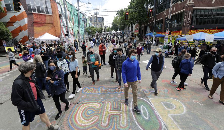 """Visitors walk near a sign that reads """"Welcome to CHOP,"""" Sunday, June 14, 2020, inside what has been named the Capitol Hill Occupied Protest zone in Seattle. Protesters calling for police reform and other demands have taken over several blocks near downtown Seattle after officers withdrew from a police station in the area following violent confrontations. The CHOP name is a change from CHAZ (Capitol Hill Autonomous Zone) that was used earlier in the week. (AP Photo/Ted S. Warren)  **FILE**"""