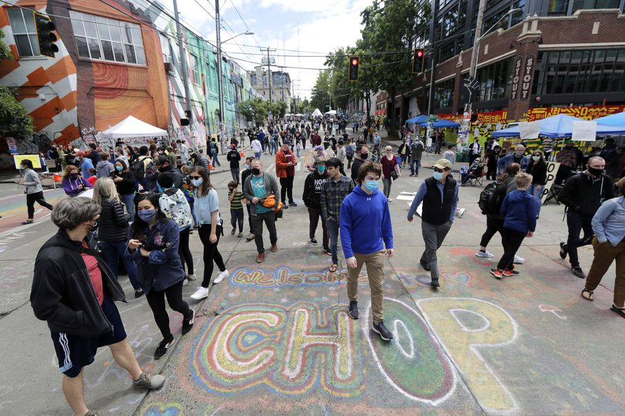 "Visitors walk near a sign that reads ""Welcome to CHOP,"" Sunday, June 14, 2020, inside what has been named the Capitol Hill Occupied Protest zone in Seattle. Protesters calling for police reform and other demands have taken over several blocks near downtown Seattle after officers withdrew from a police station in the area following violent confrontations. The CHOP name is a change from CHAZ (Capitol Hill Autonomous Zone) that was used earlier in the week. (AP Photo/Ted S. Warren)  **FILE**"