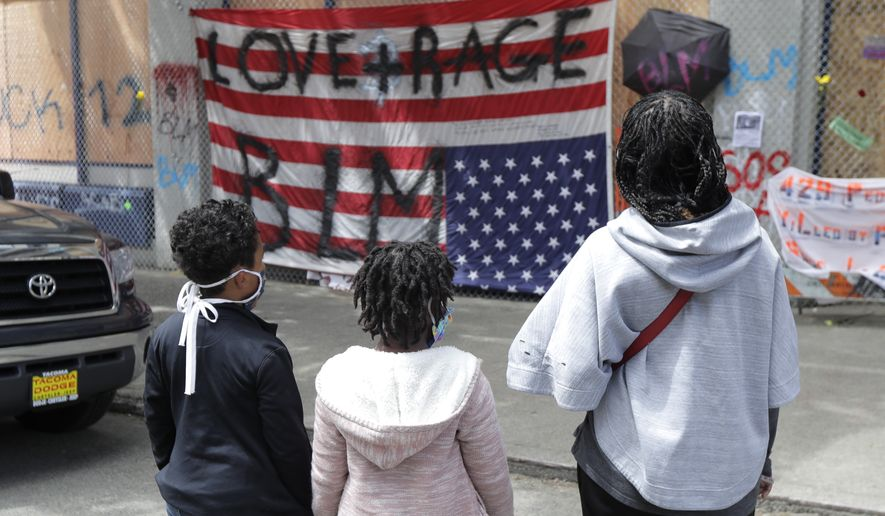"""People view an upside-down U.S. flag that has had """"Love + Rage BLM"""" painted on it, Sunday, June 14, 2020, inside what has been named the Capitol Hill Occupied Protest zone in Seattle. Protesters calling for police reform and other demands have taken over several blocks near downtown Seattle after officers withdrew from a police station in the area following violent confrontations. (AP Photo/Ted S. Warren)"""